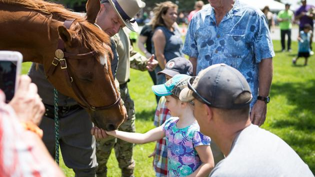 Girl greets member of the Centennial Mounted Unit.